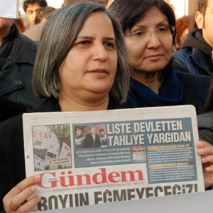 Kurdish politician holding a copy of Özgür Gündem.